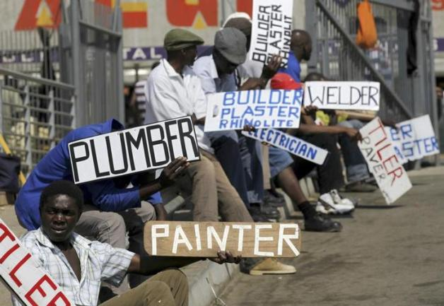 Men hold placards offering temporal employment services in Glenvista, south of Johannesburg, October 7, 2010. REUTERS/Siphiwe Sibeko (SOUTH AFRICA - Tags: BUSINESS EMPLOYMENT)